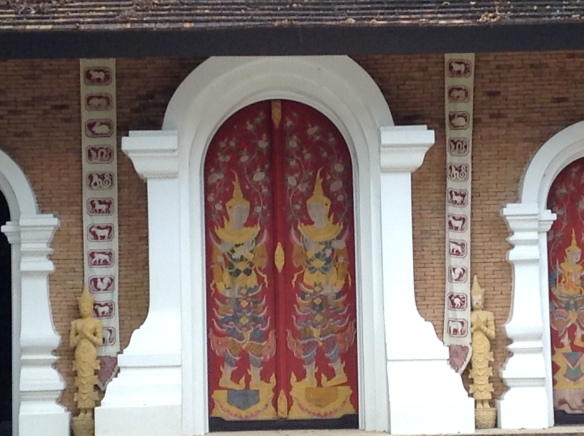 Decorative door with Thai astrological animals on the sides.