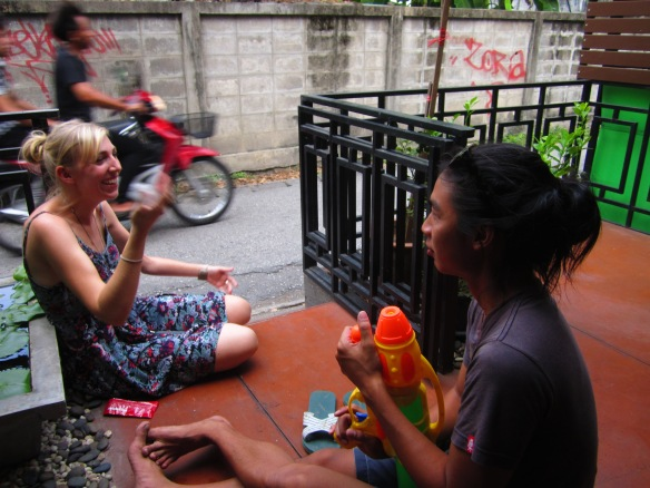 Just in time for Songkran, Thai New Year and water throwing festival. Alana laughing with Pong, who is  armed and ready.