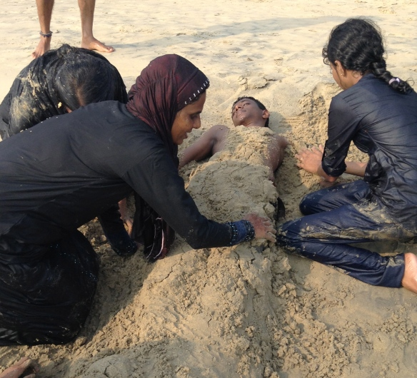 Burying and being buried in sand while fully clothed