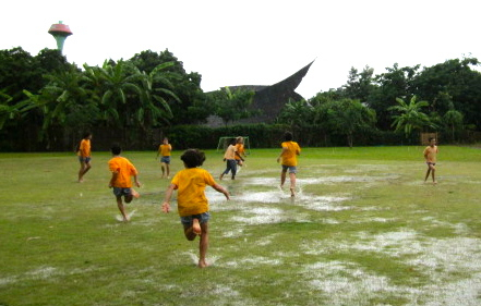 Jubilant children running through puddles.